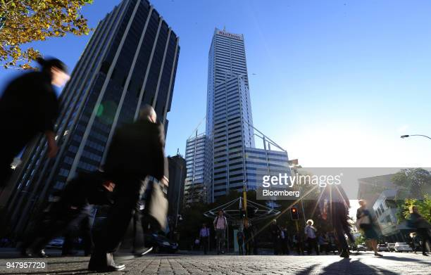 Pedestrians cross an intersection in front of Central Park Tower center in the central business district of Perth Australia on Wednesday April 11...