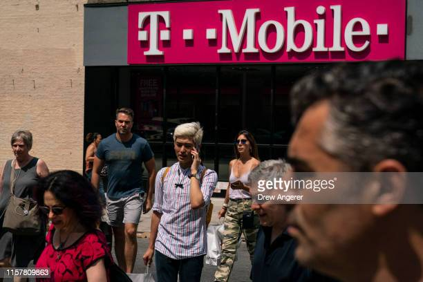 Pedestrians cross an intersection near a T-Mobile store on Sixth Avenue in Manhattan on July 26, 2019 in New York City. On Friday, the U.S....
