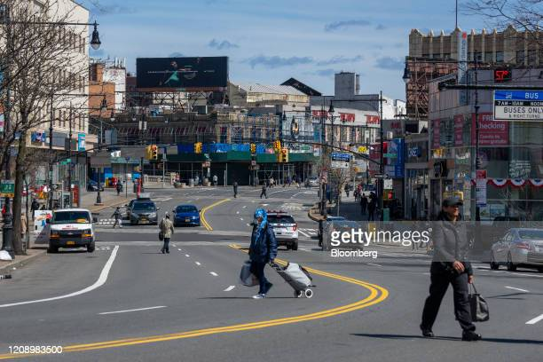 Pedestrians cross Fordham Road in the Bronx borough of New York, U.S., on Thursday, April 2, 2020. In four months, the new coronavirus infected more...