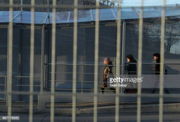 Pedestrians cross from Russia into Estonia behind a fence along the bridge over the Narva River on March 23 2017 at Narva Estonia Estonia is a member...