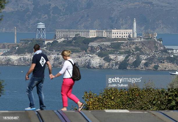 Pedestrians cross Hyde Street in front of Alcatraz Island on October 2 2013 in San Francisco California Alcatraz Island and all federal museums and...