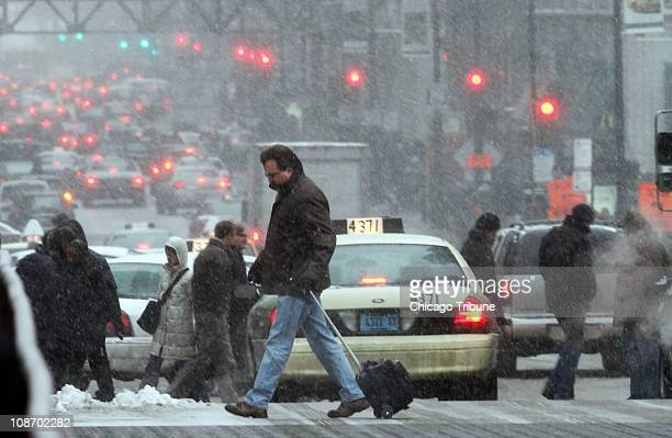 Pedestrians cross Jackson just west of Wacker Drive as snow hits Chicago Illinois Tuesday February 1 2011