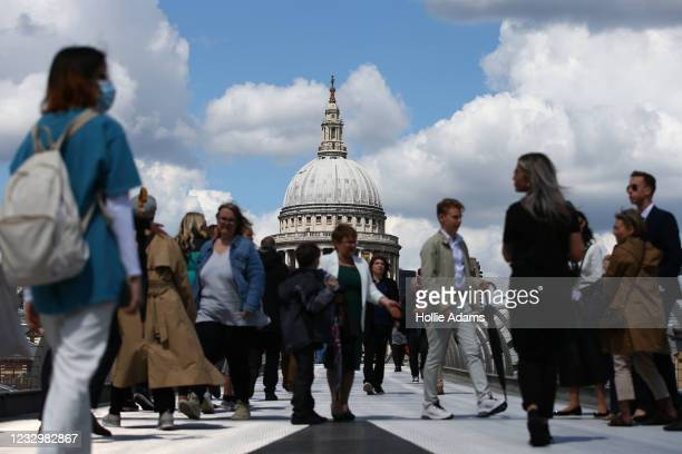 Pedestrians cross Millennium Bridge in view of St Paul's Cathedral on May 19, 2021 in London, England. Although indoor drinking and dining were...