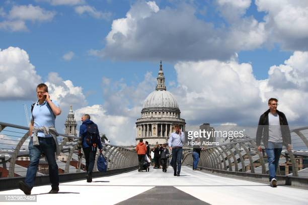 Pedestrians cross Millennium Bridge on May 19, 2021 in London, England. Although indoor drinking and dining were permitted in England with...