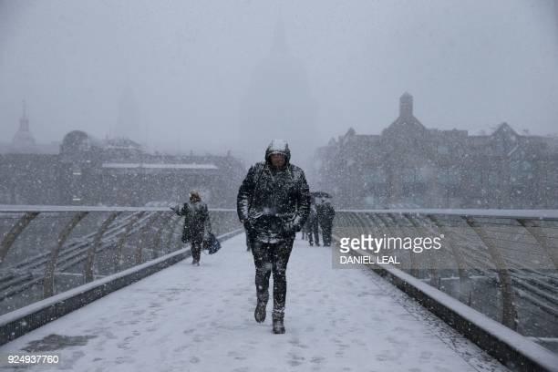 TOPSHOT Pedestrians cross the millennium bridge as heavy snowfall hits London on February 27 2018 A blast of Siberian weather sent temperatures...