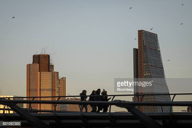 Pedestrians cross the Millennium Bridge in view of Leadenhall building also known as the 'Cheesegrater' right and Tower 42 left in London UK on...