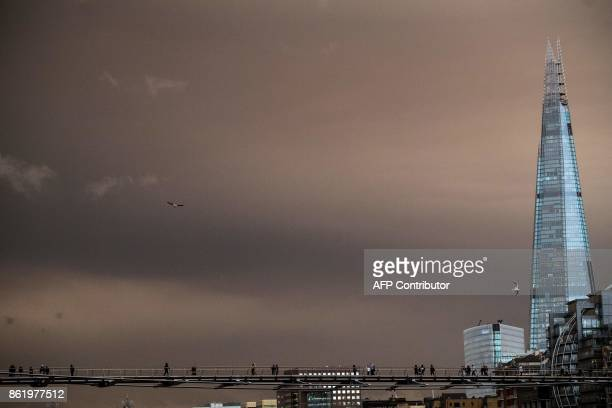 Pedestrians cross the Millennium Footbridge with the sky darkened over London on October 16 2017 caused by warm air and dust swept up by storm...