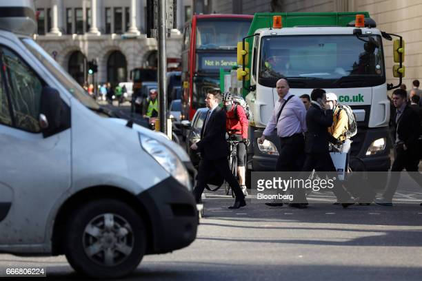 Pedestrians cross the road as vehicles wait at traffic lights in London UK on Monday April 10 2017 London has missed by seven years legal deadlines...