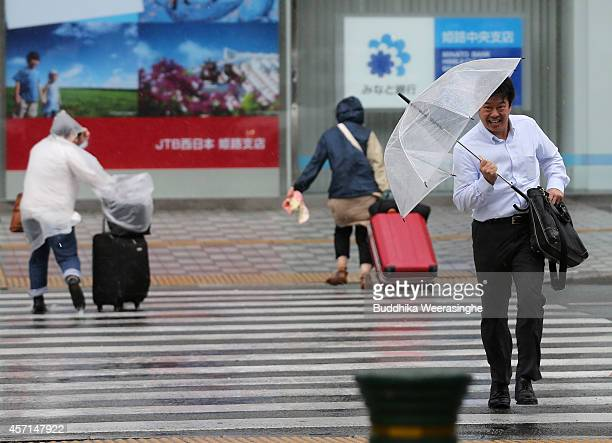 Pedestrians cross the road in the strong wind and rain delivered by Typhoon Vongfong on October 13 2014 in Himeji Japan According to the Japan...
