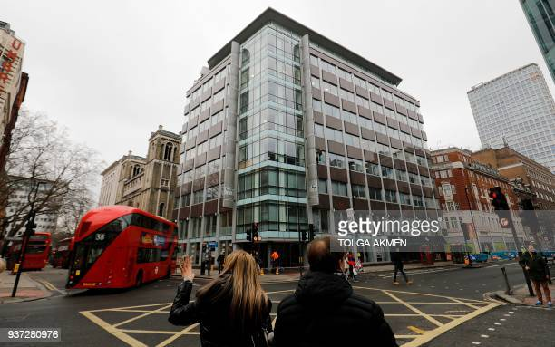 Pedestrians cross the road near outside the shared building which houses the offices of Cambridge Analytica in central London on March 24 2018...