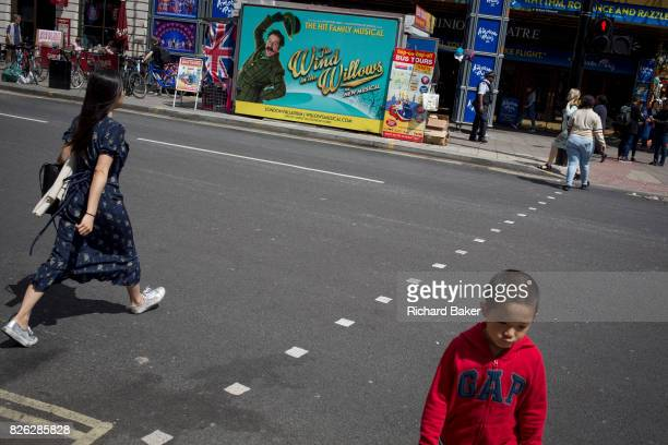 Pedestrians cross the road opposite a Wind in the Willows ad on 31st July 2017 in Tottenham Court Road London England