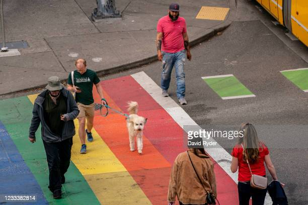 Pedestrians cross the street as Seattle has become the first major city to reach a 70 percent COVID-19 vaccination rate on June 10, 2021 in Seattle,...