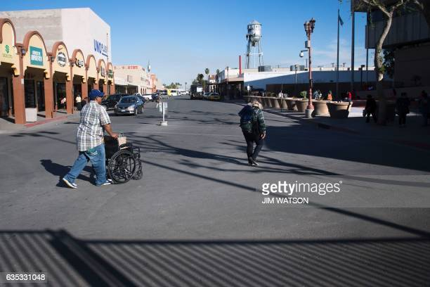 Pedestrians cross the street as they walk to the Port of Entry on the US/Mexico border in Calexico, California, on February 14, 2017. Attention...