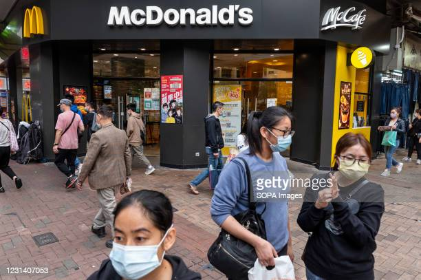 Pedestrians cross the street at a traffic light in front of the American multinational fast-food hamburger restaurant chain, McDonald's in Hong Kong.