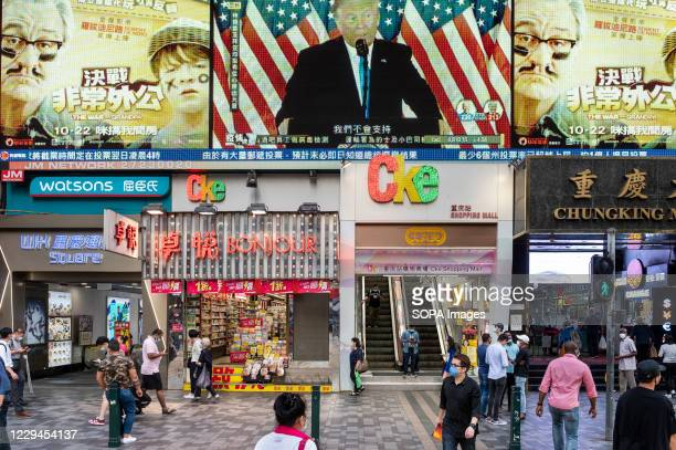 Pedestrians cross the street at a zebra crossing as Republican candidate Donald J. Trump is shown on a large screen during the live news report about...