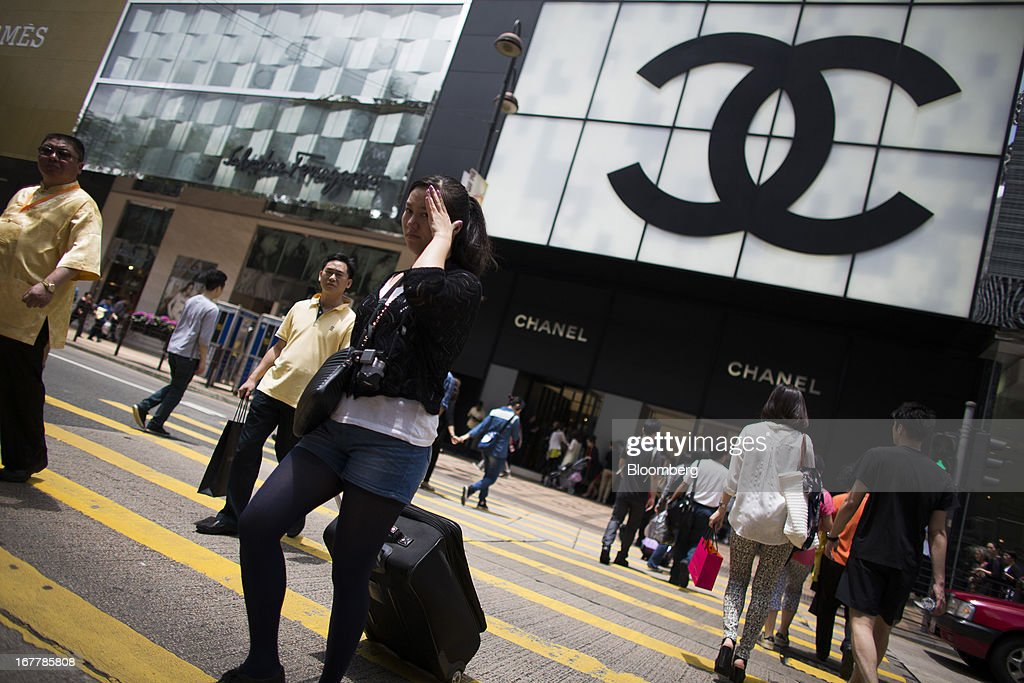 Pedestrians cross the street in front of a Chanel SA store in the Tsim Sha Tsui area of Hong Kong, China, on Tuesday, April 30, 2013. Financial Secretary John Tsang on Feb. 27 projected annual growth of 1.5 percent to 3.5 percent this year following 2012's 1.4 percent, the weakest rate since 2009 as Europe's sovereign debt crisis sapped global demand. Photographer: Lam Yik Fei/Bloomberg via Getty Images
