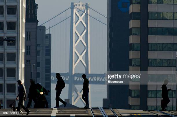 Pedestrians cross the street in front of the OaklandSan Francisco Bay Bridge in San Francisco California US on Wednesday Dec 21 2011 San Francisco...