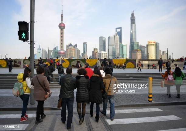 Pedestrians cross the street in Shanghai's financial district on the Bund on March 13 2014 China's industrial output rose 86 percent in January and...