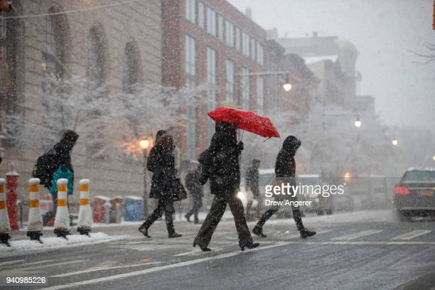 Pedestrians cross the street in the snow during the morning rush hour on Atlantic Avenue April 2 2018 in the Brooklyn borough of New York City One...