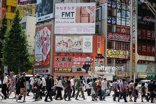 Pedestrians cross the street in Tokyo's Akihabara district on May 18 2016 in Tokyo Japan Japan's annualized GDP growth rate from January to March...