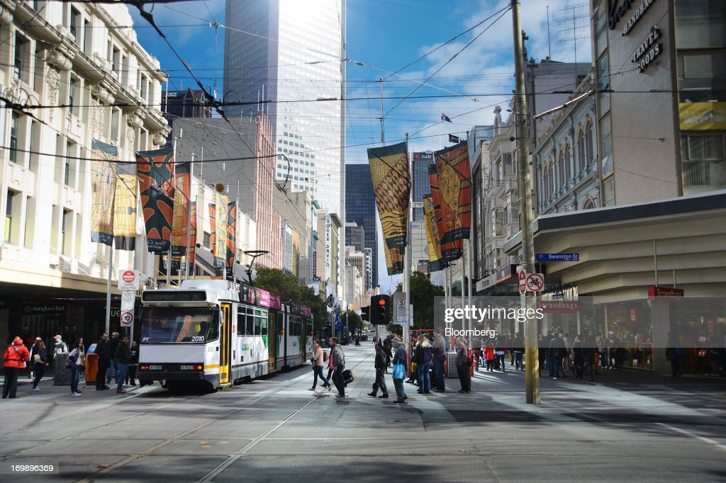 Pedestrians cross the tram tracks on Bourke Street in central Melbourne, Australia, on Sunday, June 2, 2013. The Australian Bureau of Statistics is scheduled to release first-quarter gross domestic product data on June 5. Photographer: Carla Gottgens/Bloomberg via Getty Images