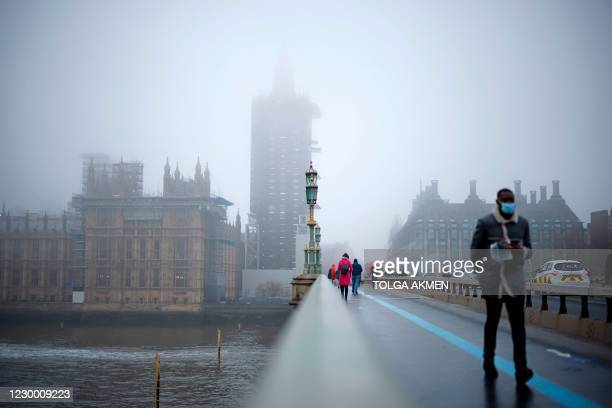 "Pedestrians cross Westminster Bridge as fog envelopes the Elizabeth Tower, commonly known by the name of the bell, ""Big Ben"", and the Palace of..."