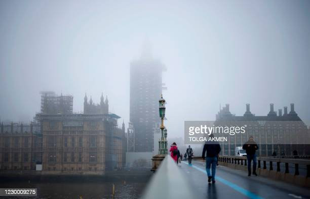 """Pedestrians cross Westminster Bridge as fog envelopes the Elizabeth Tower, commonly known by the name of the bell, """"Big Ben"""", and the Palace of..."""