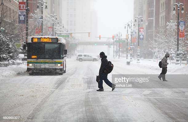 Pedestrians cross Woodward Avenue as it snows as the area deals with record breaking freezing weather January 6 2014 in Detroit Michigan Michigan and...