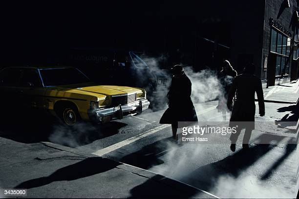 Pedestrians crossing a New York street in winter time cast long shadows 1980