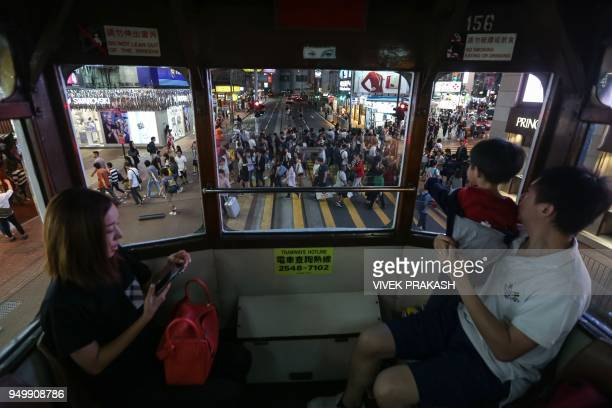 Pedestrians crossing a road are seen through the windows of a tram in Hong Kong on April 22 2018