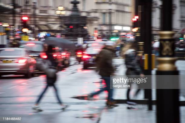 pedestrians crossing a street in the rain - red light stock pictures, royalty-free photos & images