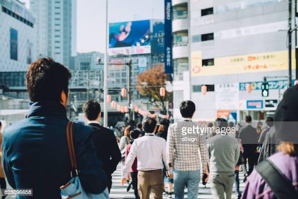 Pedestrians crossing street in downtown Tokyo, Japan