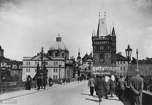 Pedestrians crossing the Charles Bridge over the Vltava river in Prague Czechoslovakia circa 1935 On the left is the Holy Crucifix