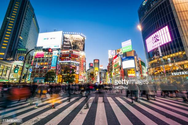 pedestrians crossing the street at shibuya crossing with motion blur - japan stock pictures, royalty-free photos & images