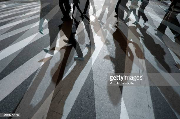 pedestrians crossing the street - pedestrian stock pictures, royalty-free photos & images