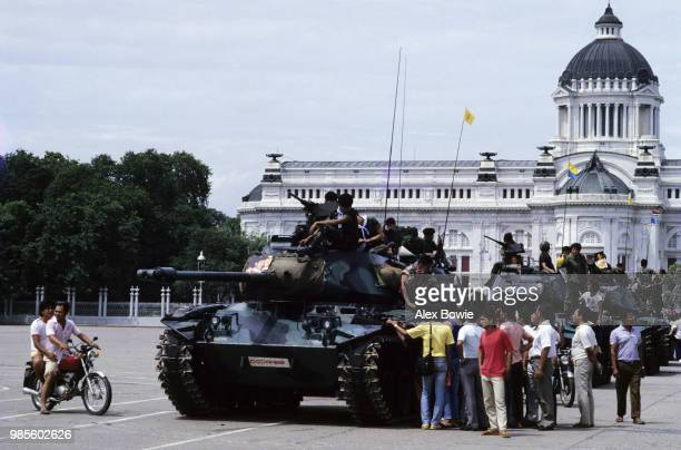 Pedestrians crowd around a column of tanks manned by Thai government soldiers outside Bangkok's old parliament house following supression of the coup...