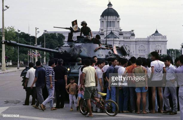 Pedestrians crowd around a tank manned by soldiers loyal to the Thai government outside Bangkok's old parliament house following supression of the...