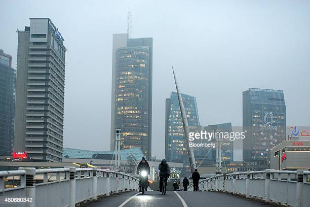 Pedestrians cycle across a bridge over the River Neris in early morning light in Vilnius Lithuania on Tuesday Dec 16 2014 Lithuania will switch...