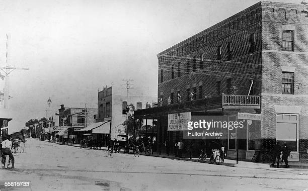 Pedestrians cyclists and horsecarriages are seen along the view East on Flagler Street in downtown Miami Florida circa 1900 A large banner hangs from...
