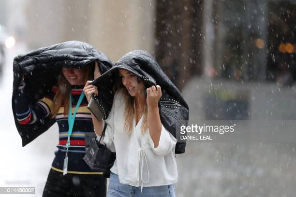 Pedestrians dash through the streets of central London during a downpour on August 10 2018