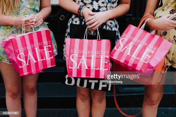 Pedestrians display Victoria's Secret Stores LCC shopping bags for a photograph in the SoHo neighborhood of New York US on Wednesday June 18 2014 The...