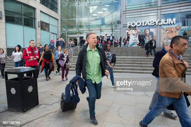 Pedestrians evacuate the Arndale shopping mall in Manchester UK on Tuesday May 23 2017 At least 22 people were killed in a suicide bombing at a pop...