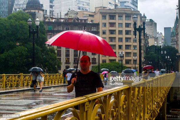 Pedestrians face rain on viaduct in central Sao Paulo Brazil on 19 March 2018