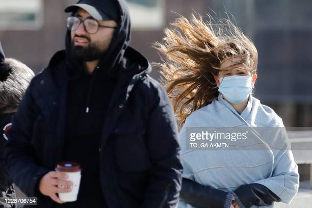 Pedestrians face windy conditions as they cross London Bridge in central London on September 25, 2020. - The country is seeing a marked change in the...