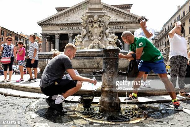 Pedestrians fill their bottles with water from a Nasone typical Roman fountain in front of The Pantheon in central Rome on July 28 2017 Two years of...