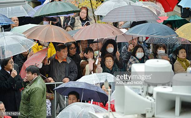 Pedestrians gather for a campaign speech of the ruling Democratic Party of Japan for the House of Representatives election in Iwaki Fukushima...