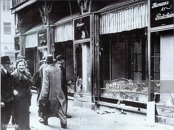 Pedestrians glance at the broken windows of a Jewish owned shop in Berlin after the attacks of Kristallnacht November 1938