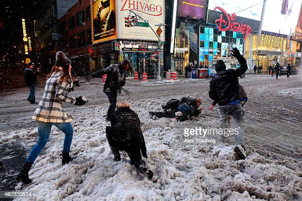 Pedestrians have a snowball fight in Times Square following a mandatory shutdown of the streets at 11 pm on January 26 2015 in New York City New York...