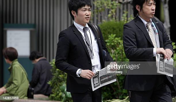 Pedestrians hold copies of an extraedition newspaper reporting the launch of a North Korean rocket in Tokyo Japan on Friday April 13 2012 The North...