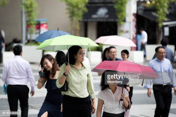 Pedestrians holding umbrella walk through the central business district of Singapore on Wednesday June 13 2018 Tourism as well as the consumer sector...